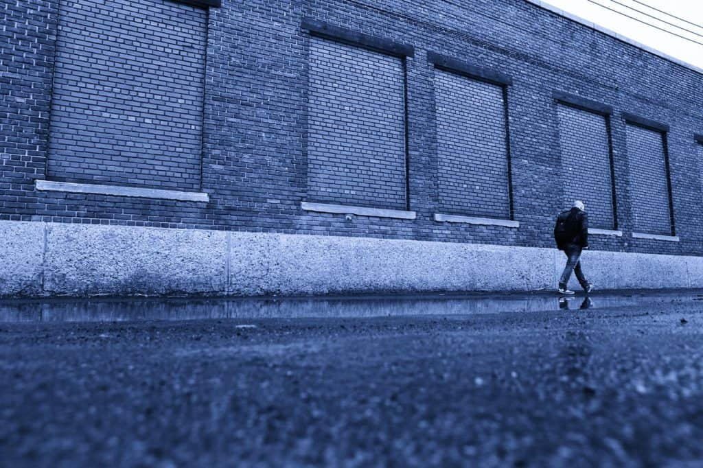man walking in front of blue warehouse