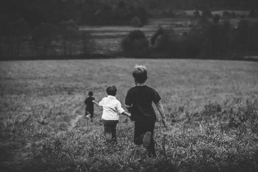 Boys running in a field.