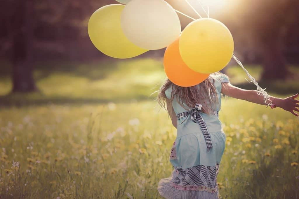 Girl running with balloons in a field.