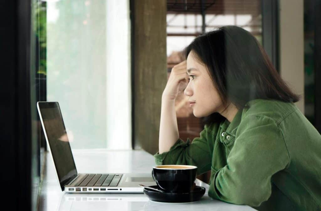 """Woman looking pensively at open laptop. From the article """"Staying productive as a writer"""" available on Dreamers Creative Writing."""